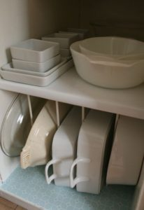 using tension rods to organize bakeware