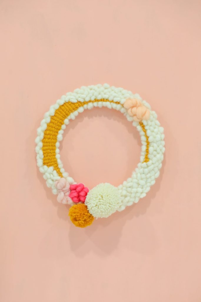woven yarn spring wreath with pom poms