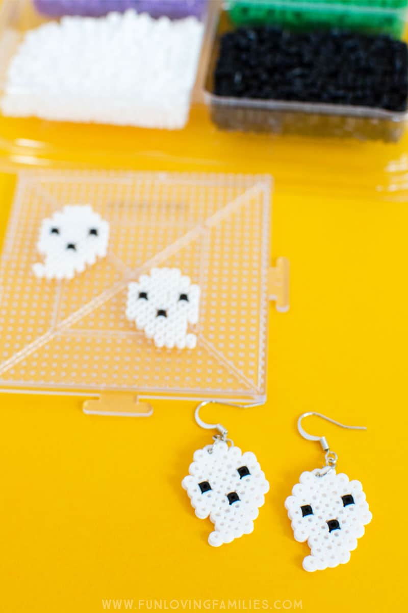 These cute little DIY ghost earrings are perfect for Halloween! #halloweenDIY #perlerbeads #fusebeads #fusebeadcrafts #perlerbeadcrafts #meltybeadcrafts #halloweencraft #halloweenjewely #tweencrafts #teencrafts #funlovingfamilies