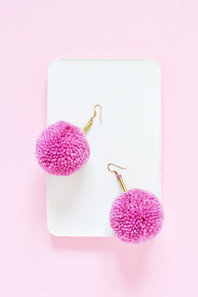 pink poofy pom pom earrings on white tray with pink background