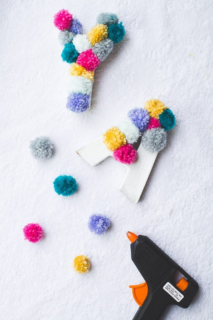 colorful pom pom letters and hot glue gun