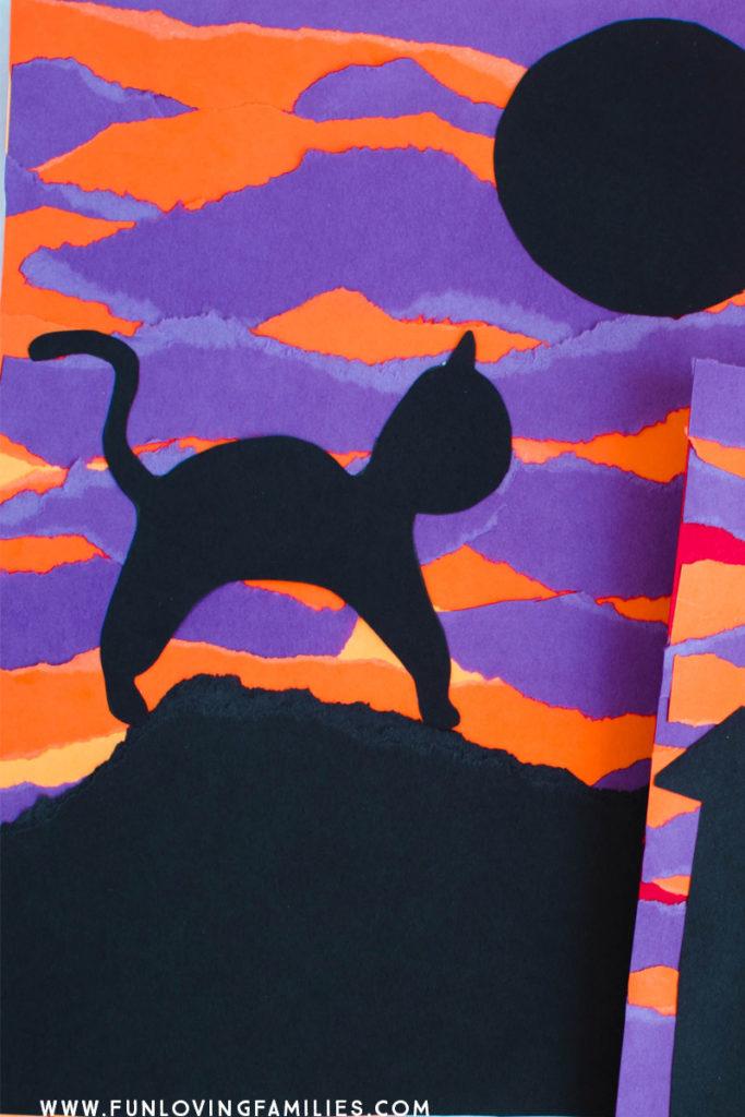 black cat on purple and orange torn paper background