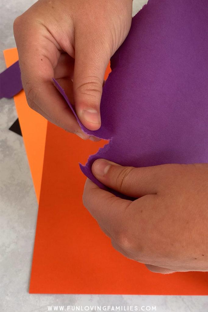 hands tearing purple paper