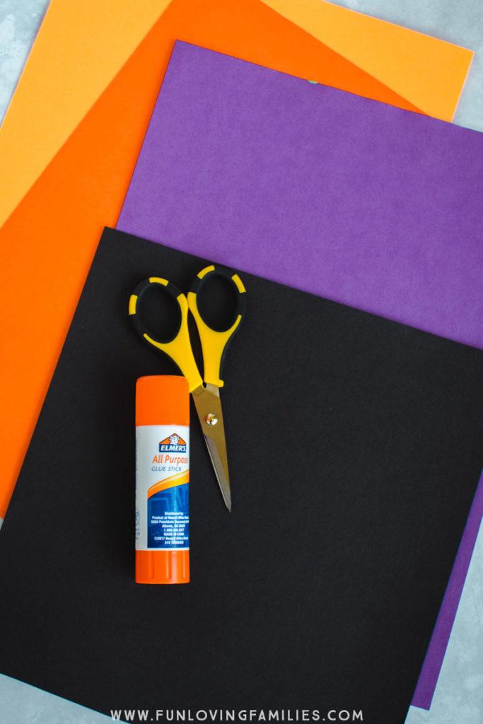 orange, purple, and black paper with scissors and glue stick