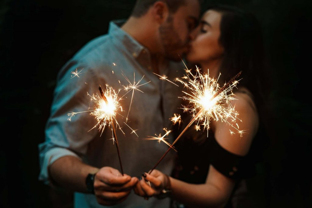 Couple kisses holding sparklers on romantic summer night